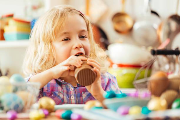kleine mädchen essen schokolade osterhasen - kinderschokolade stock-fotos und bilder