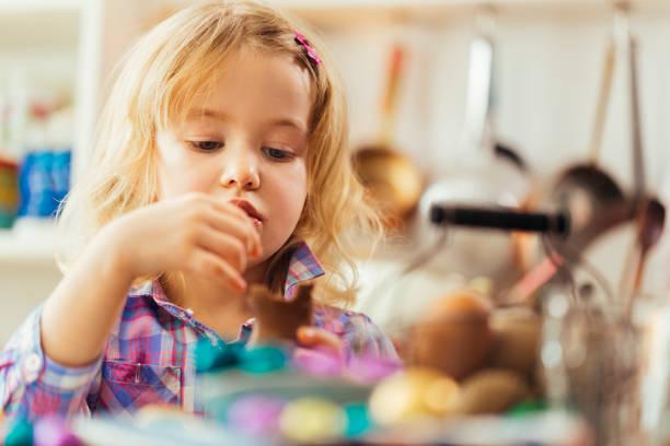 little girl eating chocolate easter bunny - buona pasqua in tedesco foto e immagini stock