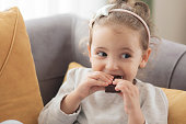 Little girl eating chocolate at home