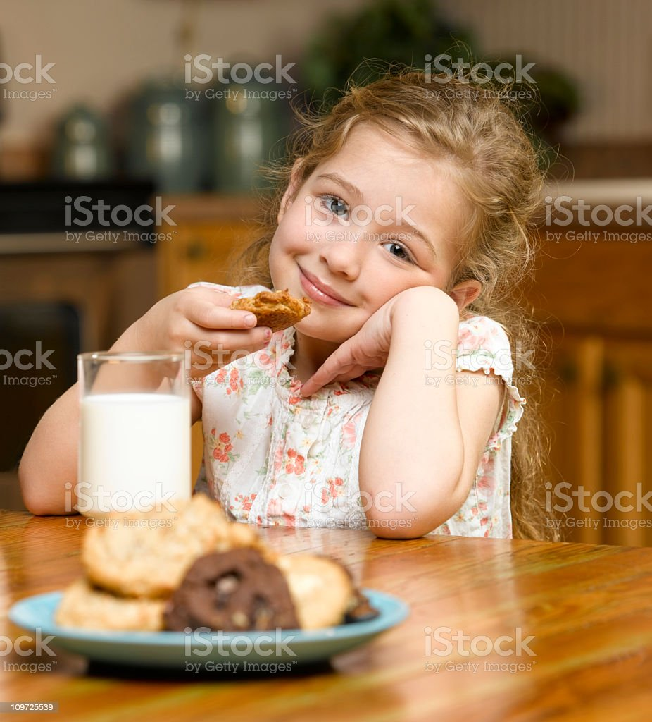 Little Girl Eating Cookies and Milk royalty-free stock photo