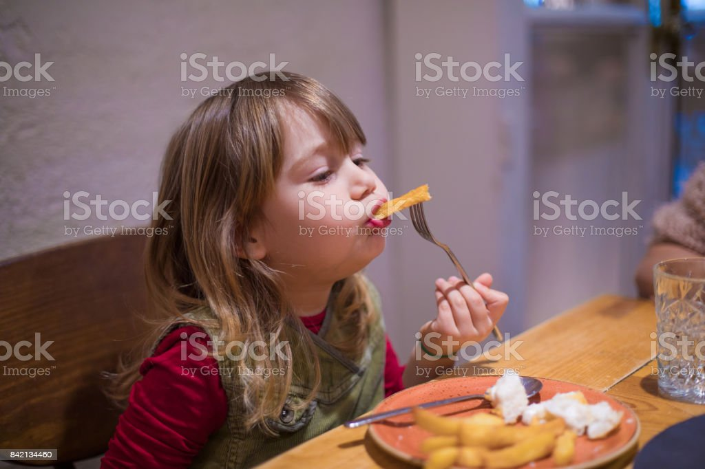 little girl eating french fries with fork stock photo