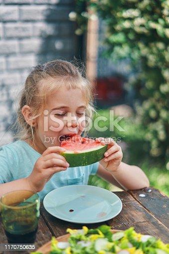 Little Girl Eating Fresh Watermelon in the Garden Outside