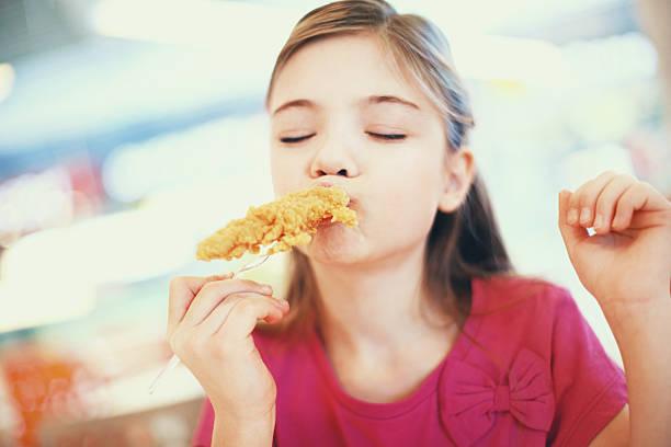 Bambina mangiare pollo fritto. - foto stock