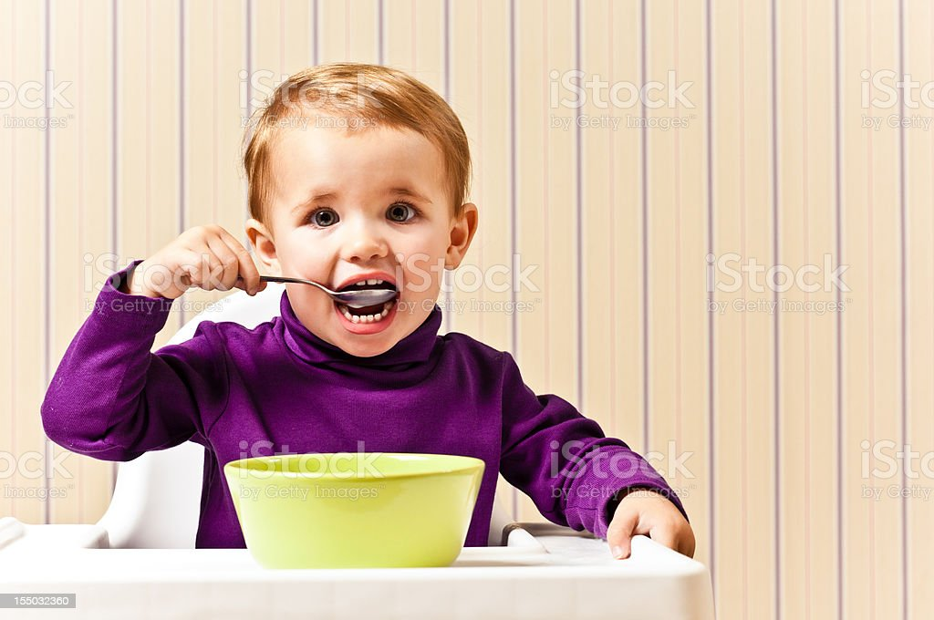 Little Girl eating from cereal bowl royalty-free stock photo