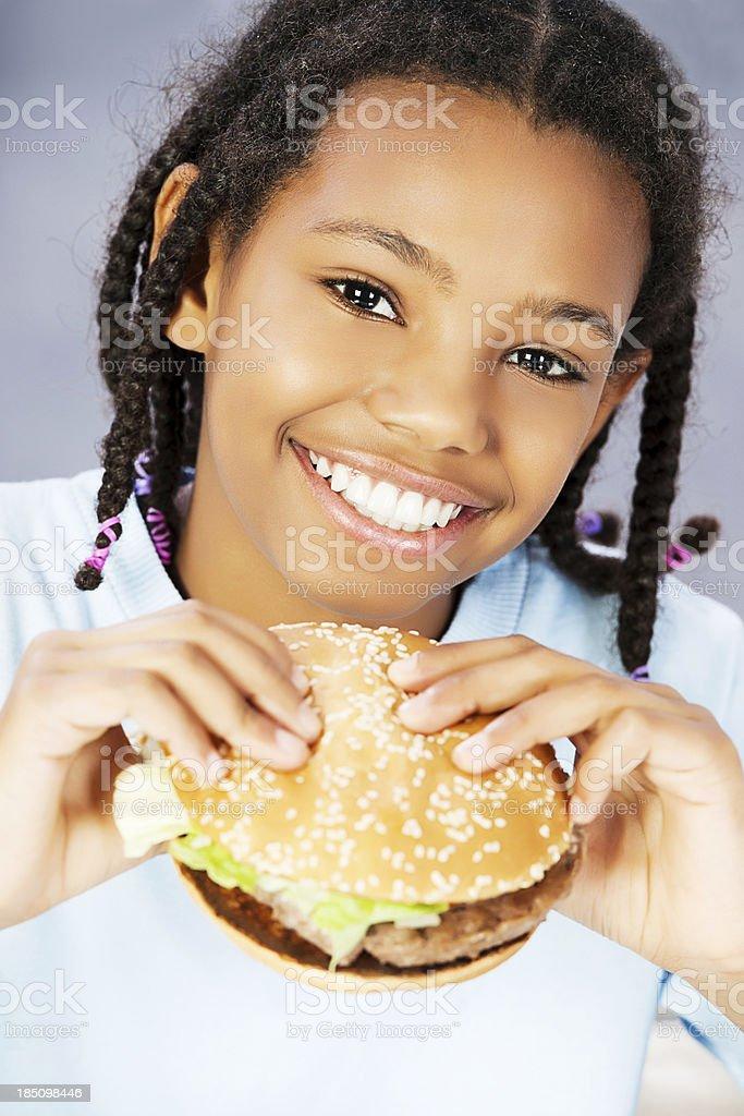 Little girl eating hamburger, enjoying fast food royalty-free stock photo