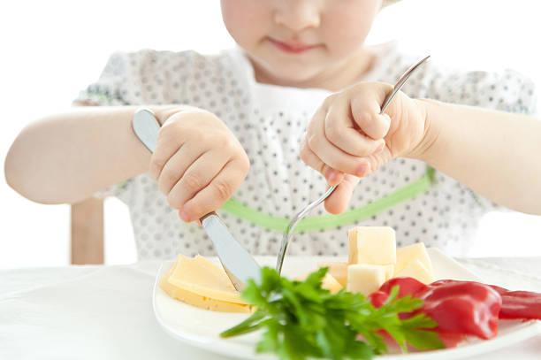 little girl eating her dinner - bordsskick bildbanksfoton och bilder