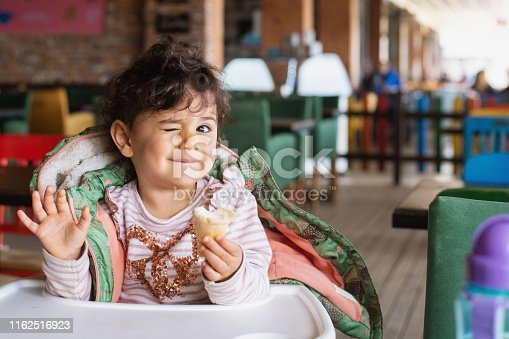 A little girl sitting in her high chair, eating ice-cream.