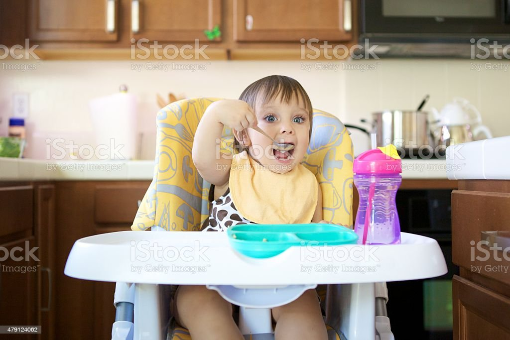Little Girl Eating in High Chair stock photo