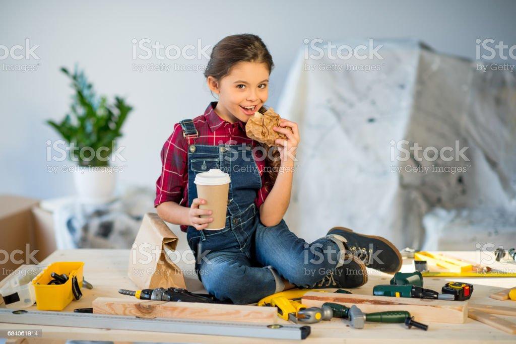 Little girl eating in workshop stock photo