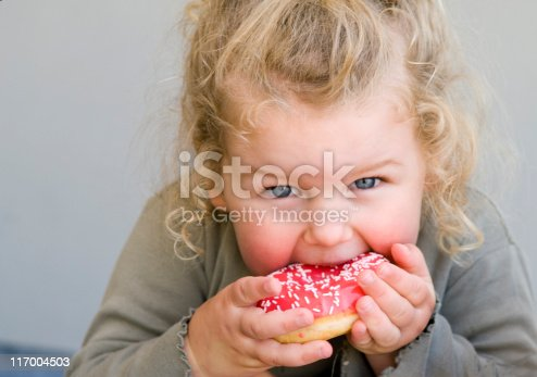 Young girl aged 2 to 3 years eating donut with pink icing