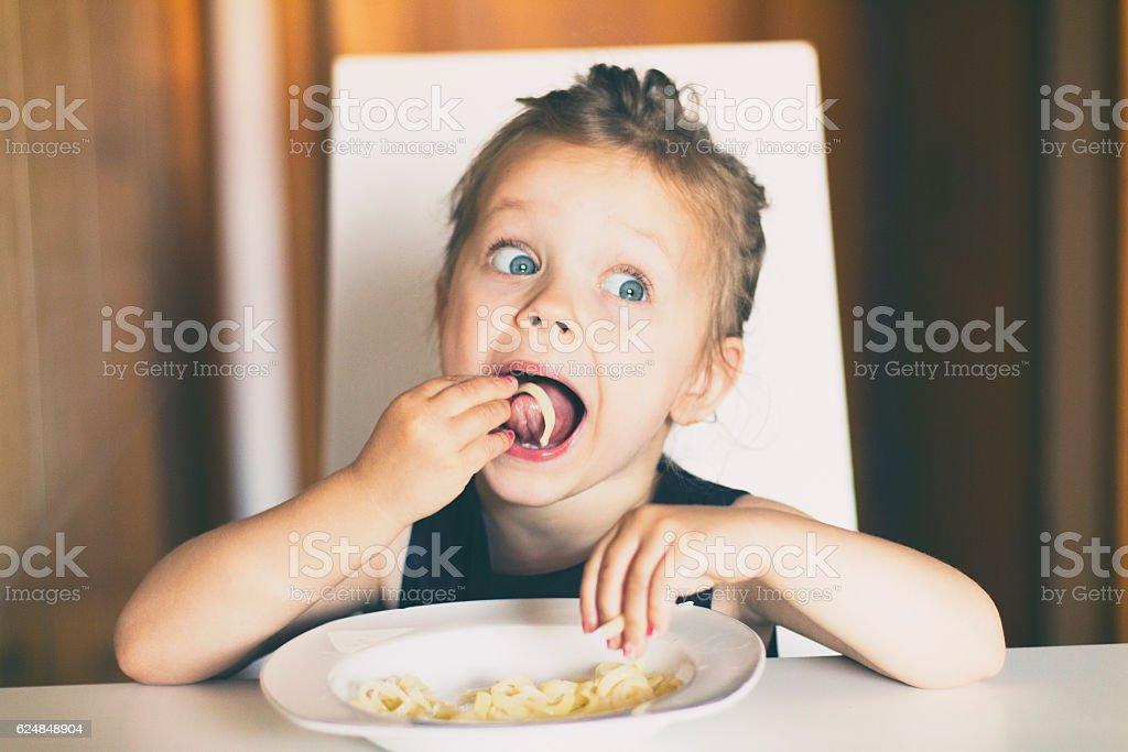 Dziewczynka jedzenie Makaron – zdjęcie