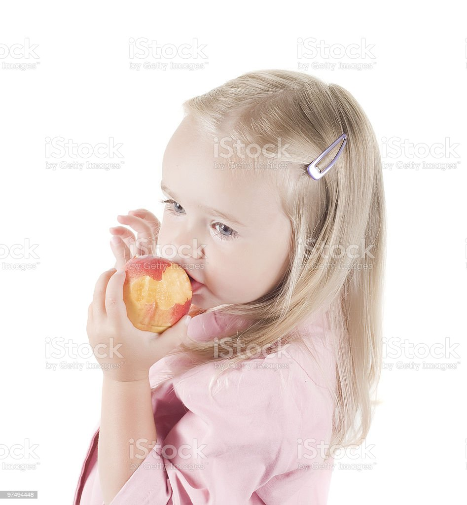 Little girl eating peach in studio royalty-free stock photo