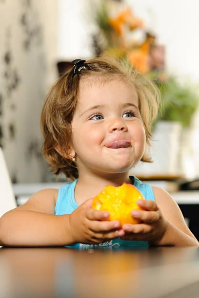 bambina mangiare - pesche bambino foto e immagini stock