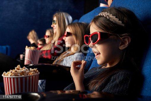 istock Little girl eating popcorn, watching cartoon in cinema. 1147577710