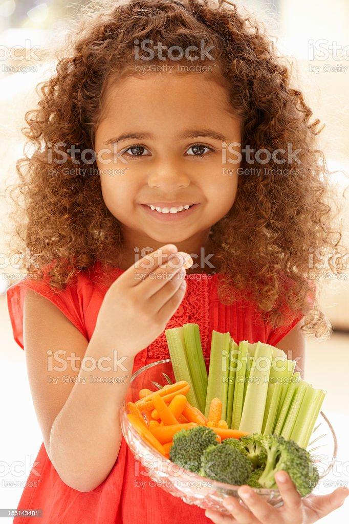 Little girl eating raw vegetables stock photo
