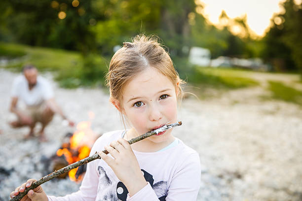 kleines mädchen isst gebratene marshmallow - kindergrill stock-fotos und bilder