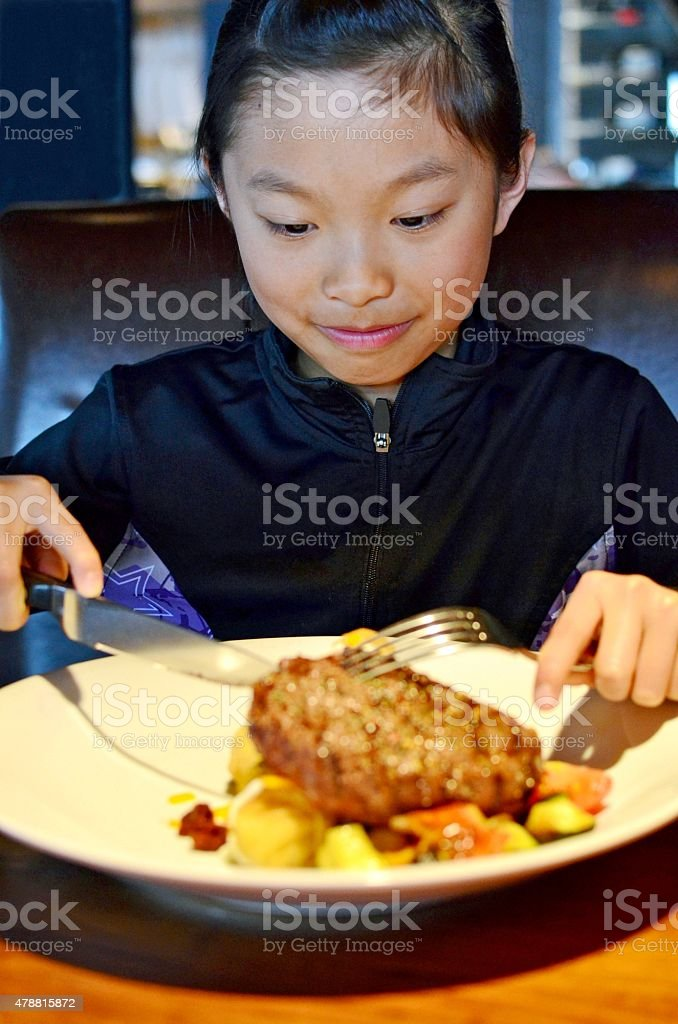 Little girl eating steak stock photo