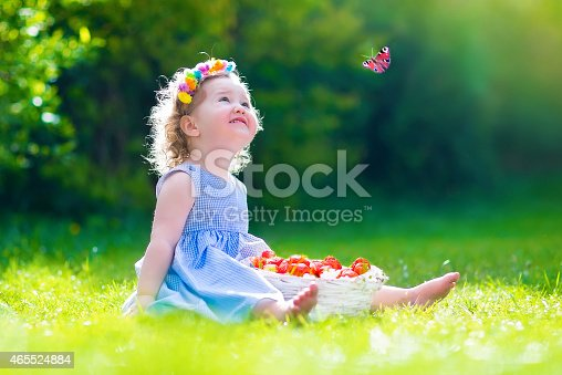 istock Little girl eating strawberry watching a butterfly 465524884