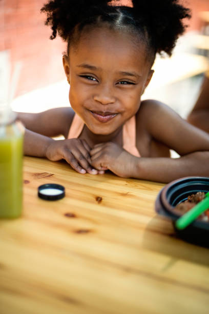 Little girl eating take out food outdoors. stock photo