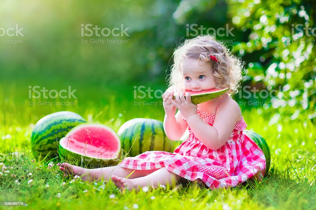 Little girl eating watermelon stock photo