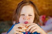 Little girl eats a cheese sandwich