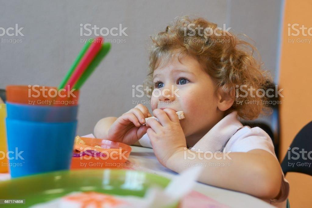 Little Girl Eats Rice Cake stock photo