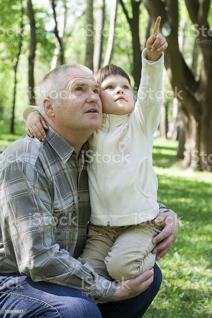 Little girl embraces grandfather, sits on arms and points up royalty-free stock photo
