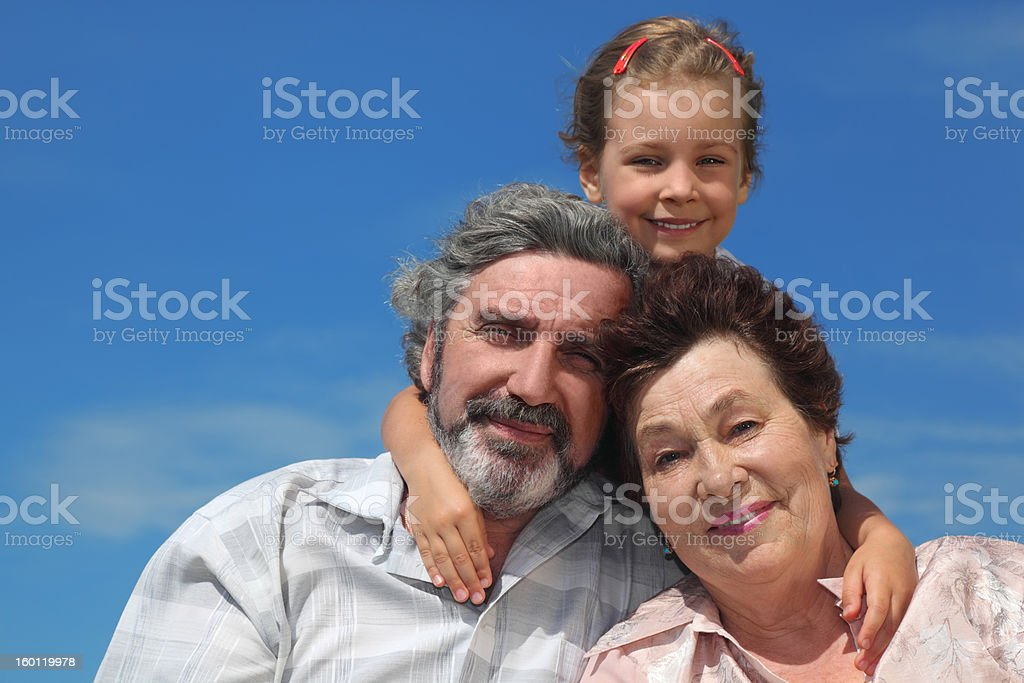 Little girl embracing her grandparents from back and smiling royalty-free stock photo