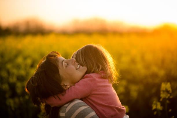 Kleines Mädchen umarmt ihre Mutter im Feld Raps – Foto