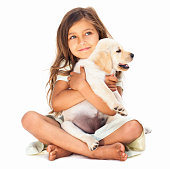 Cute little girl holding her pet affectionately, looking into copy space.