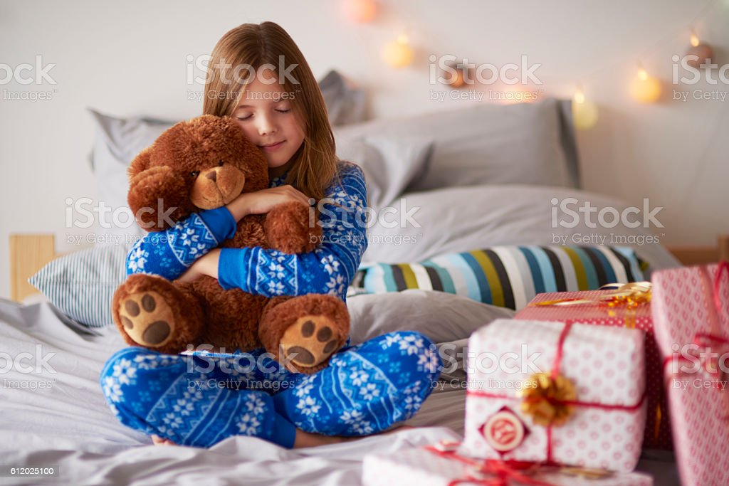 Little girl embracing teddy bear at Christmas stock photo