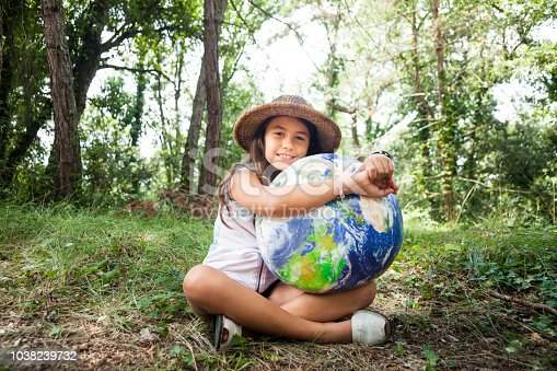 I love my planet: Young scout girl embracing world globe.
