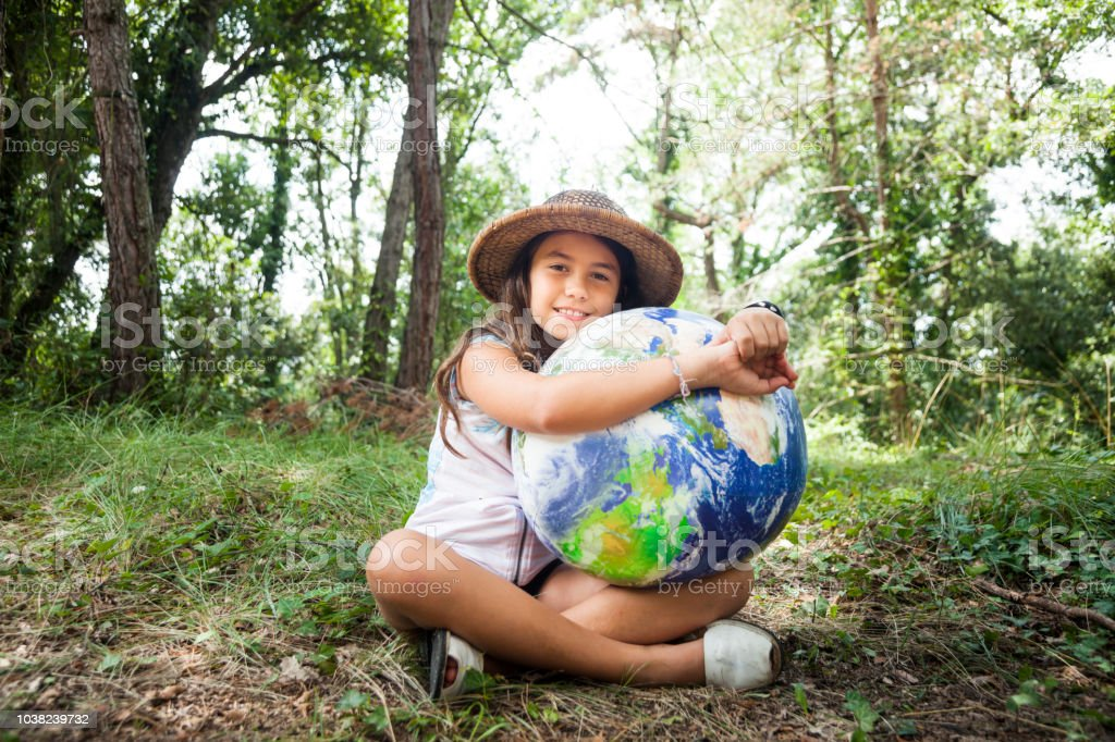 Little girl embracing world globe stock photo