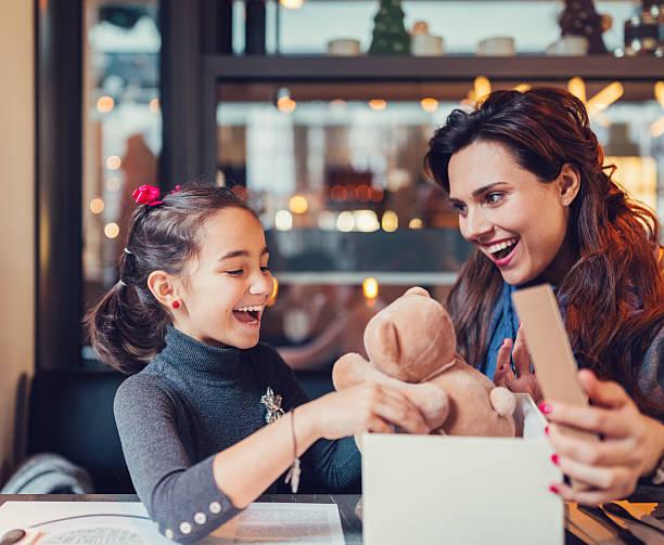 little girl enjoying a birthday gift - geschenke eltern weihnachten stock-fotos und bilder