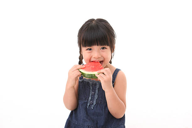 A little girl enjoying a slice of watermelon stock photo