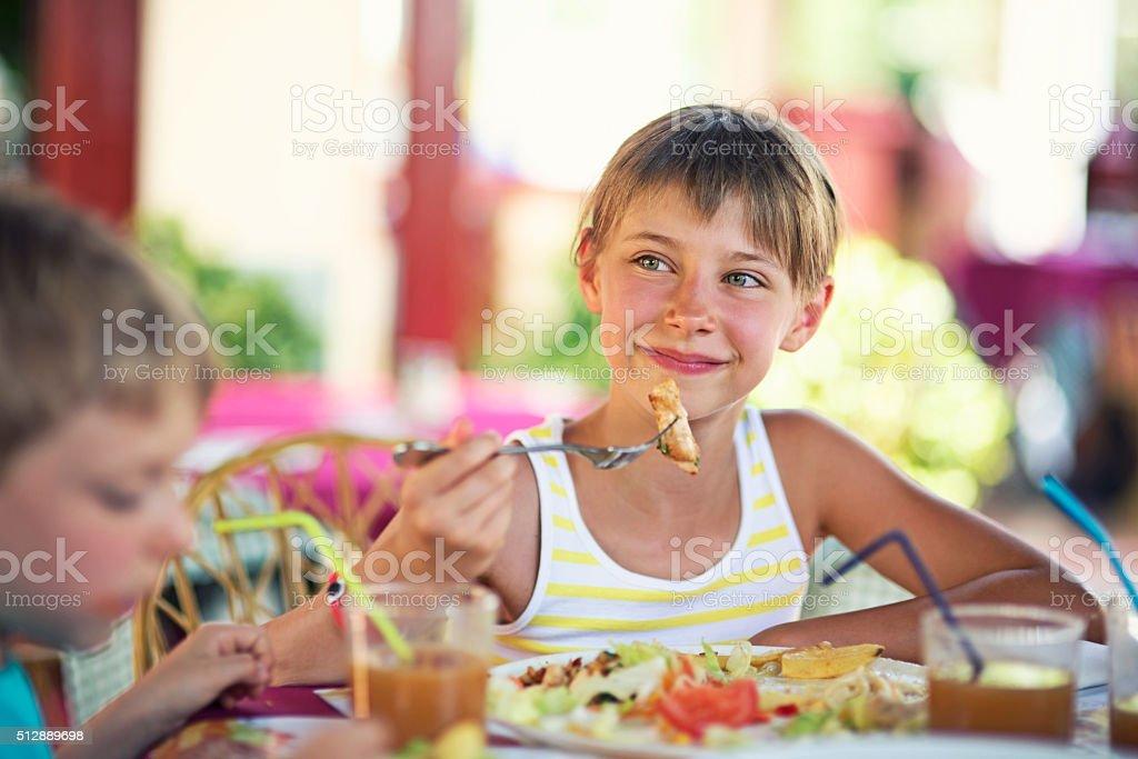 Little girl enjoying dinner in restaurant with family stock photo