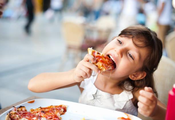 Little Girl Enjoying her Meal stock photo