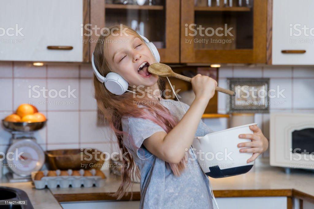 Kleines Mädchen, das Musik genießt, während es in der Küche Essen zubereitet - Lizenzfrei 2019 Stock-Foto