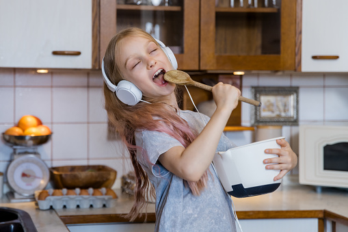 Little girl listeing music in headphones and preparing food in kitchen