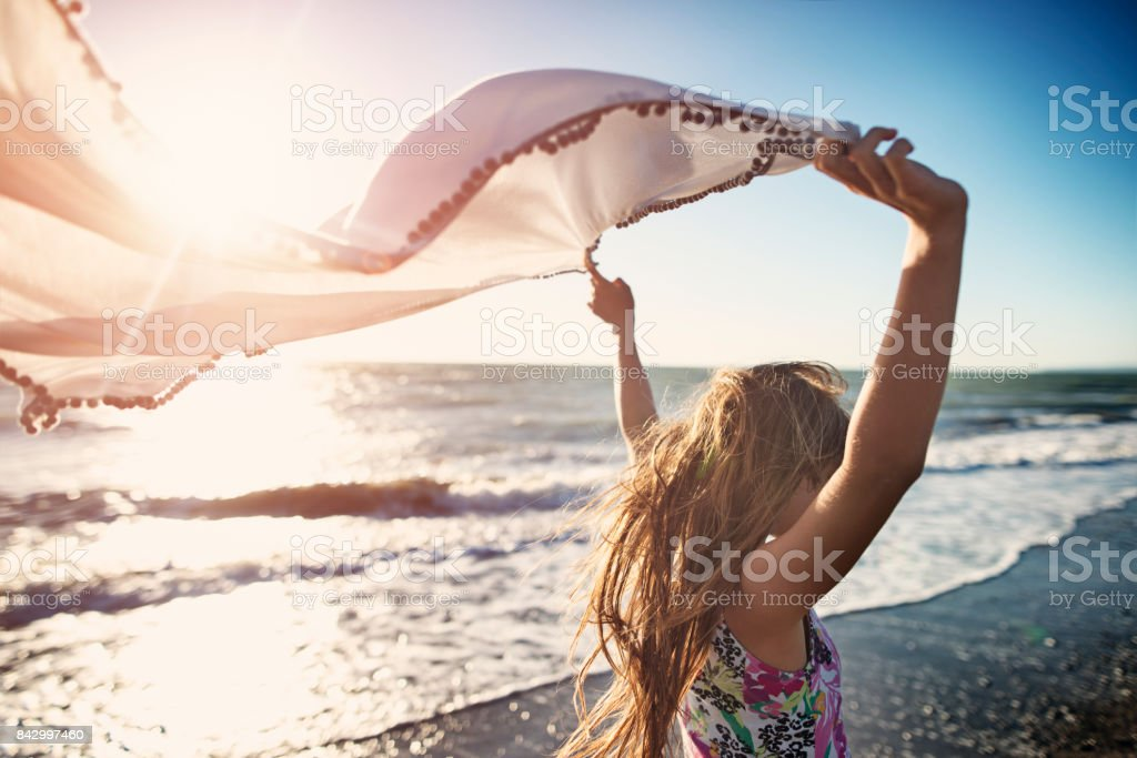 Little girl enjoying sunset on a windy beach stock photo
