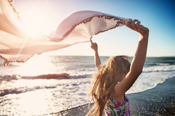 little girl enjoying sunset on a windy beach - wind stock photos and pictures