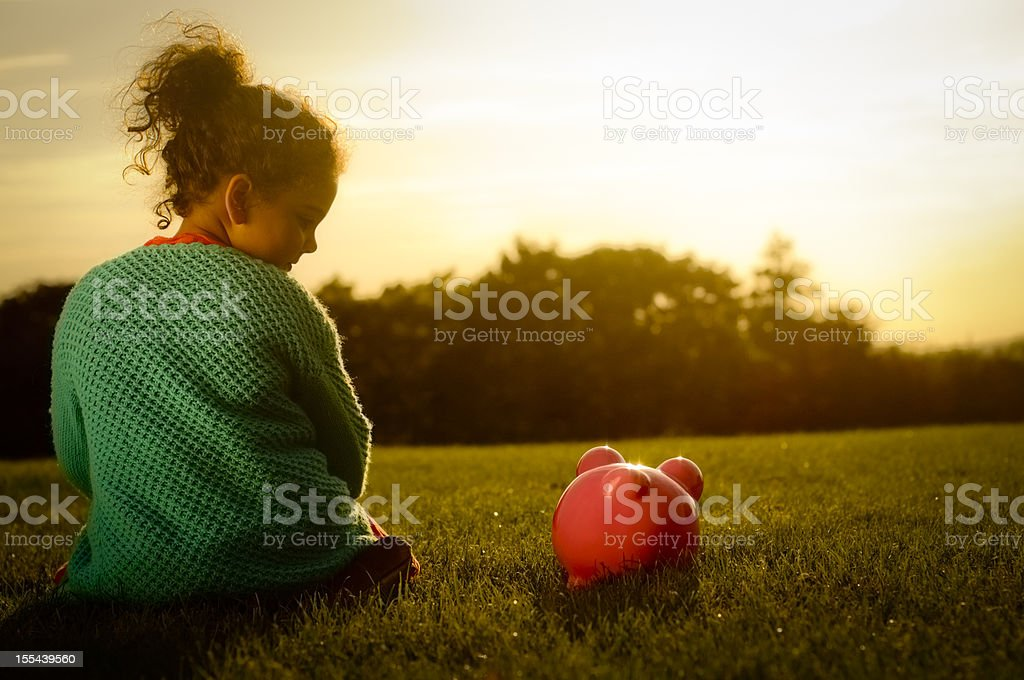 Little girl enjoying sunset with her piggy bank royalty-free stock photo