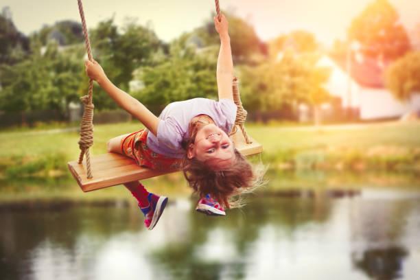 Little girl enjoying swinging in countryside stock photo