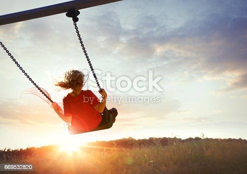 Child enjoying swinging in sunset light