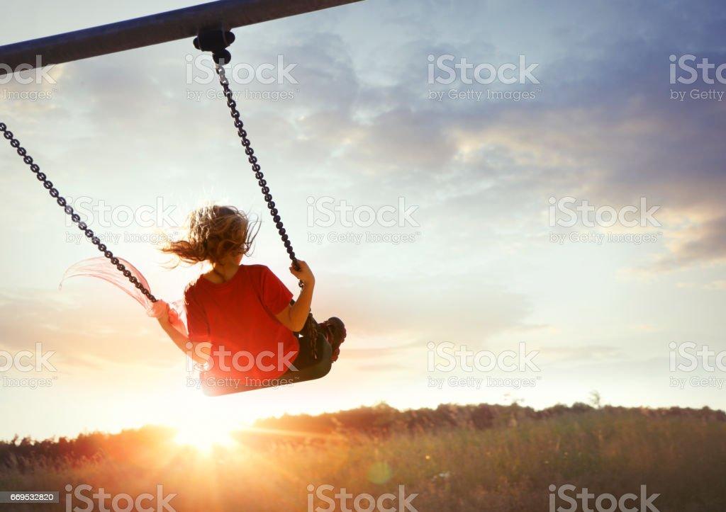 Little girl enjoying swinging stock photo