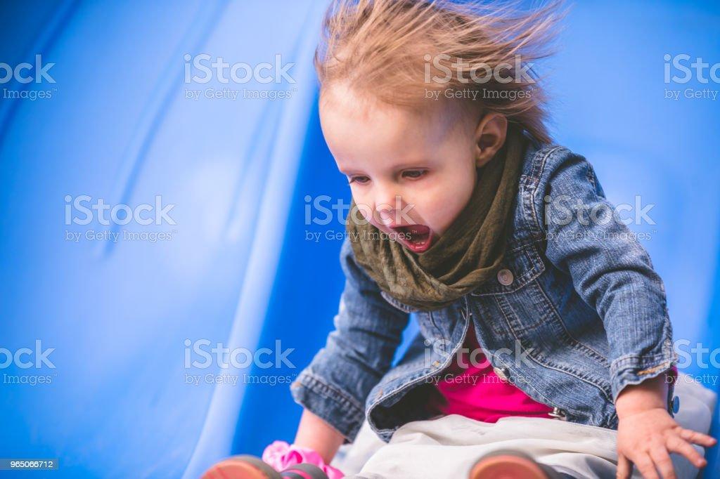 Little girl enjoying the slide at the park zbiór zdjęć royalty-free