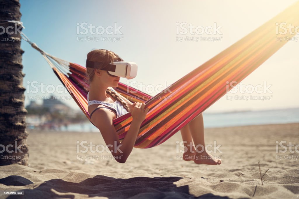 Little girl enjoying Virtual Reality beach stock photo