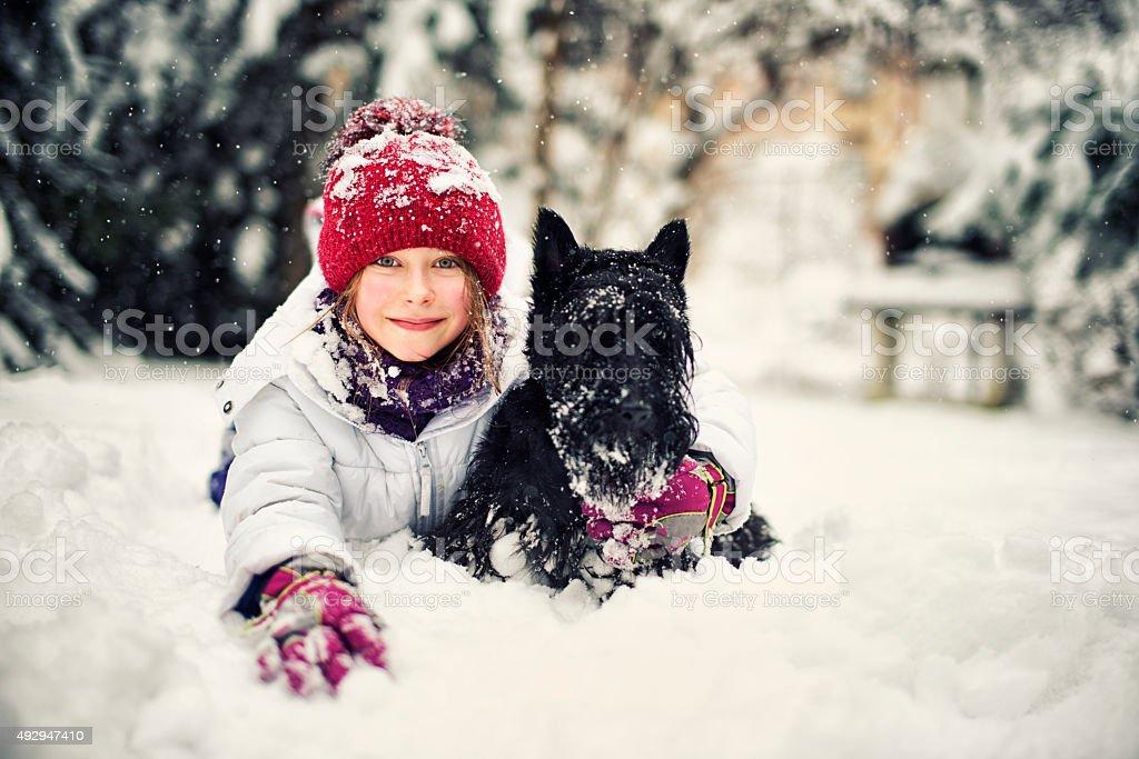 Little girl enjoying winter with her dog. stock photo