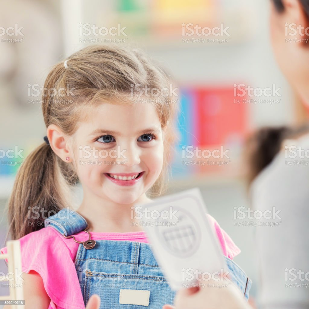 Little girl enjoys game with day care worker stock photo