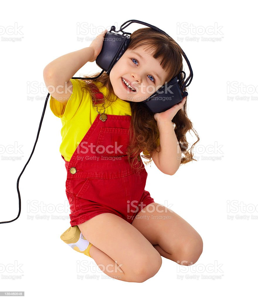 Little girl enjoys music in big headphones royalty-free stock photo